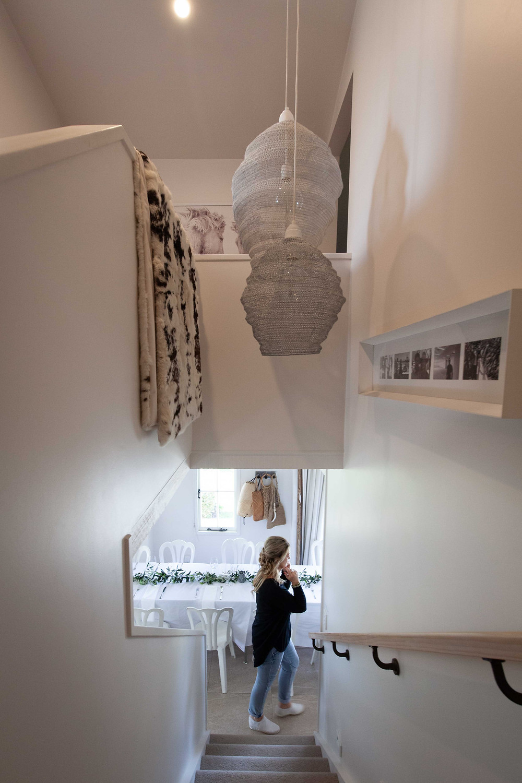 inside with artwork and lady walking past stairs, wedding accommodation Olivio~nor, Martinborough Wairarapa