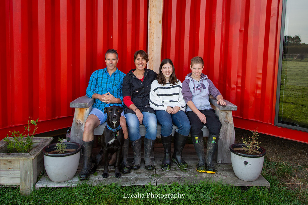 The Hicks family including pet dog sitting in front of their container home, Wairarapa