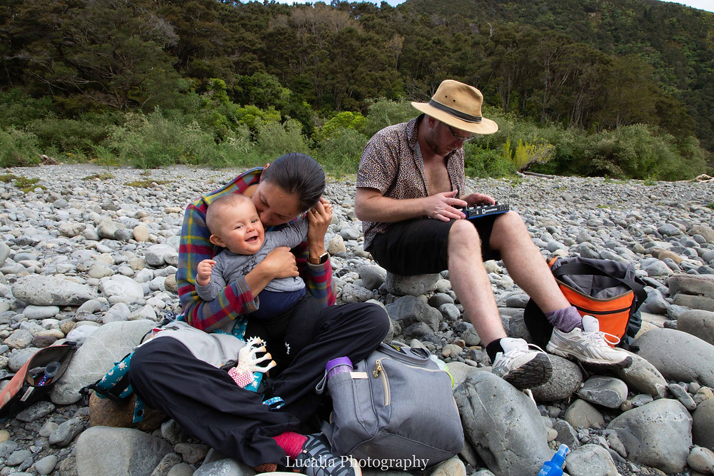 mum holding and kissing 6 month old baby sitting on riverbank with dad playing a synth, Tararua Forest Park, Wairarapa family photographer