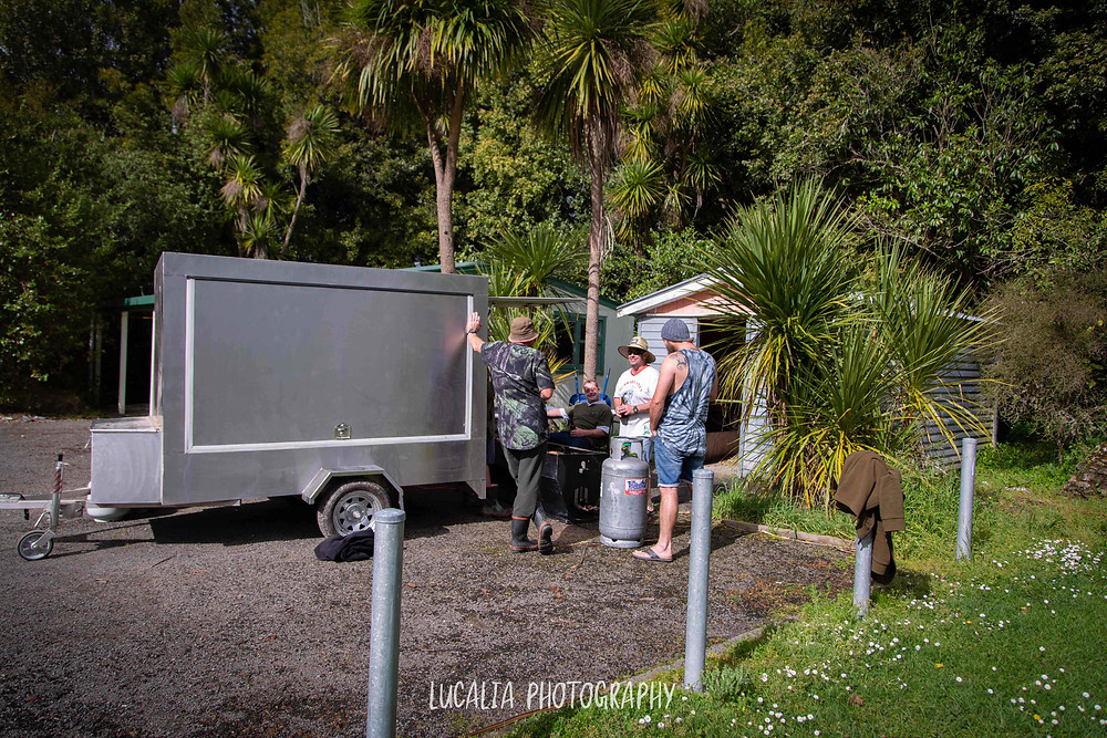 groom and best man standing outside with portable kitchen, Wairarapa wedding photographer