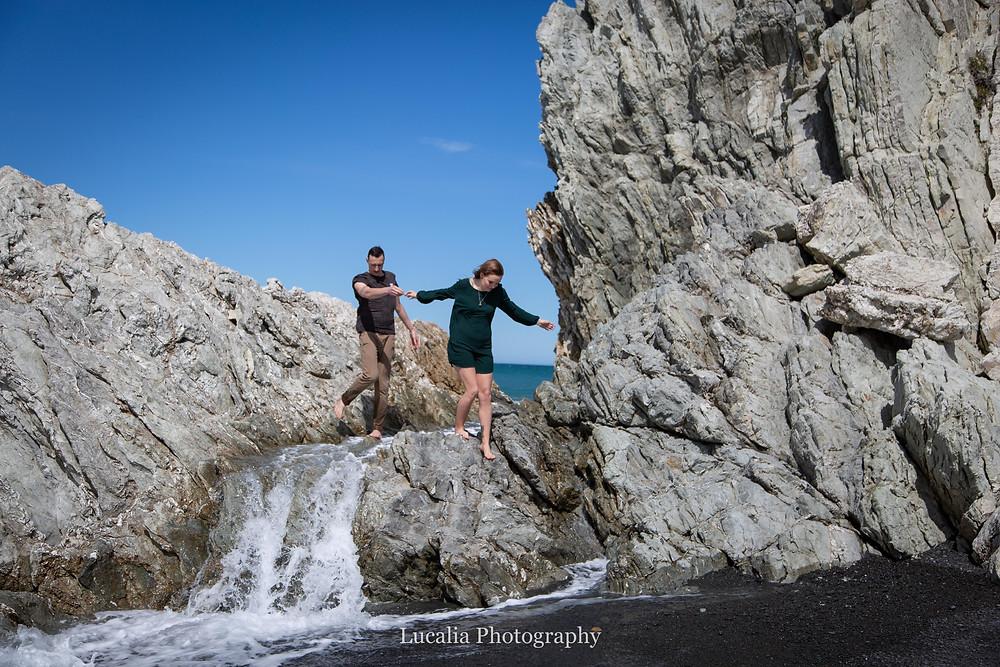wedding couple climbing on White Rock beach, Wairarapa wedding photographer