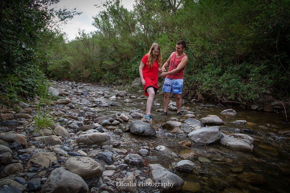 engaged couple walking over rocks in a river bed, Featherston Wairarapa