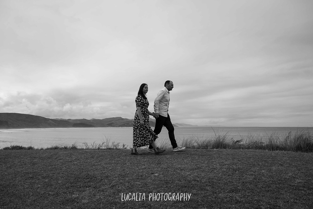 engaged couple walking outside their bach at Castlepoint, Lucalia Photography Wairarapa wedding photographer