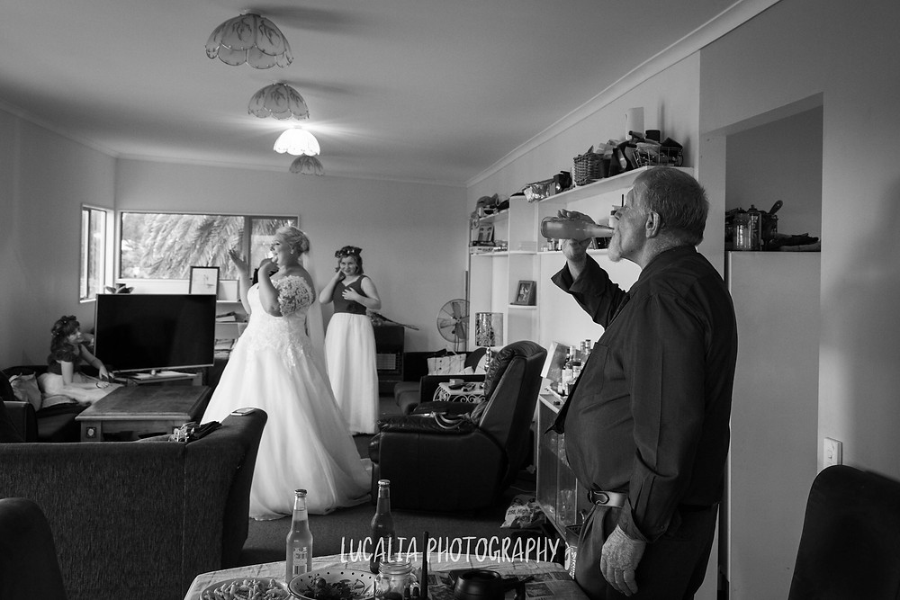 father of the bride drinking a beer with his daughter in background, Ngawi Wairarapa wedding photographer