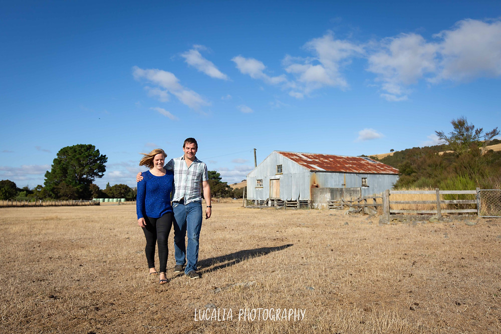 engaged couple walking in a field with old woolshed in background, Martinborough Wairarapa wedding photographer