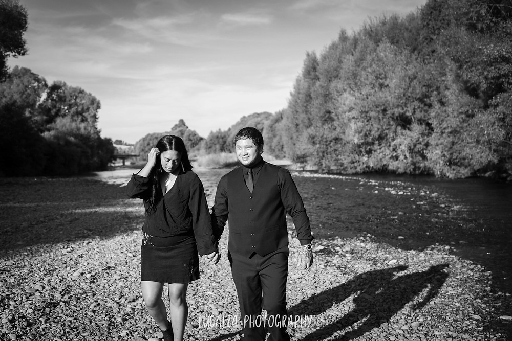 engaged couple walking along river bank, Henley Lake, Masterton, Wairarapa wedding photographer