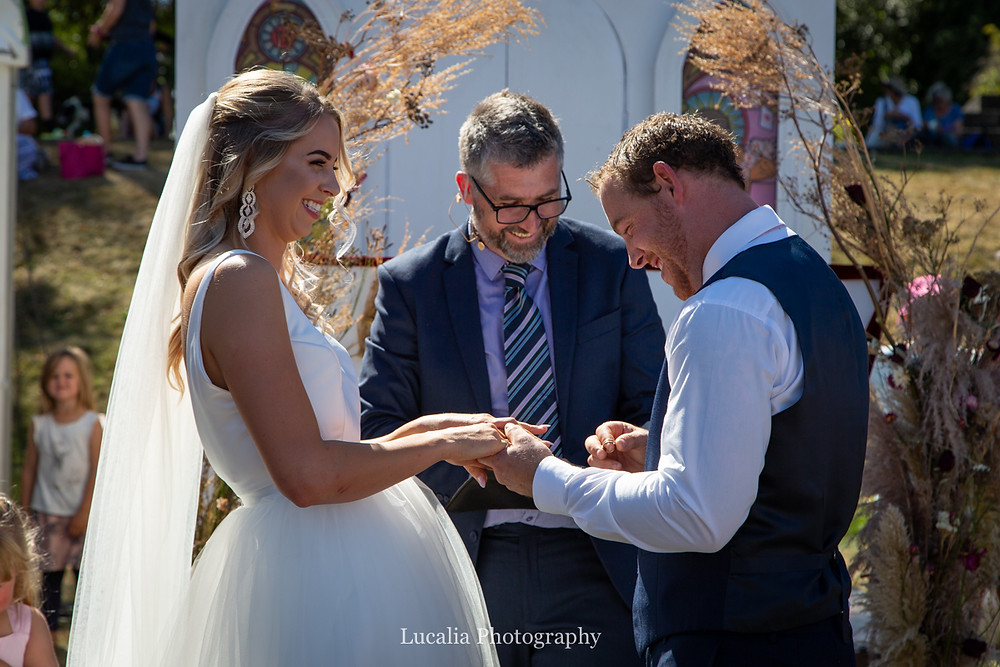 bride laughing as groom has trouble putting on her wedding ring, Wairarapa