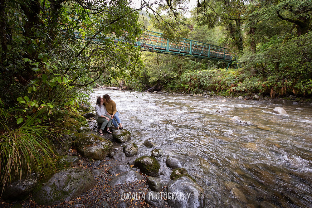 engaged couple sitting on a rock kissing beside the river at Mt Holdsworth with bridge in the background, Wairarapa photographer
