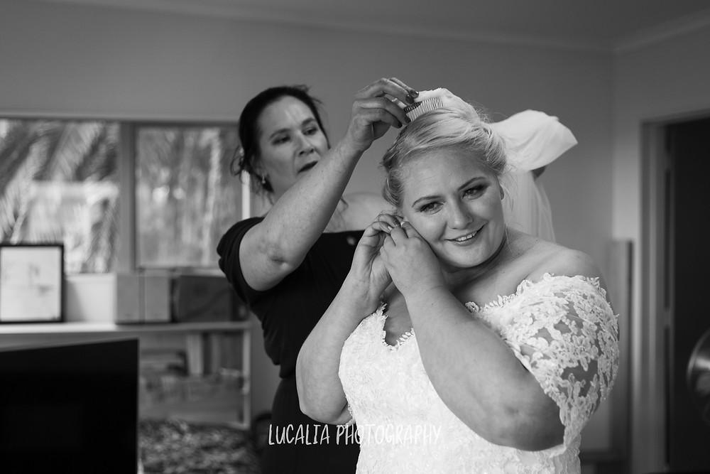 friend helping bride put on her veil, Ngawi Wairarapa wedding photographer