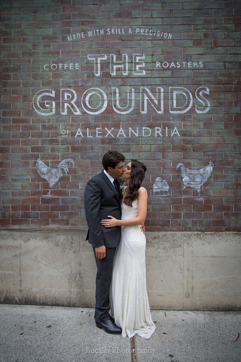 bride and groom kissing in front of brick wall