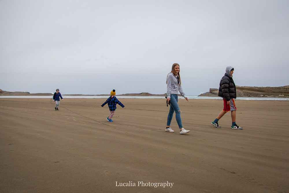 cousins walking along Castlepoint beach, Castlepoint Wairarapa family photographer