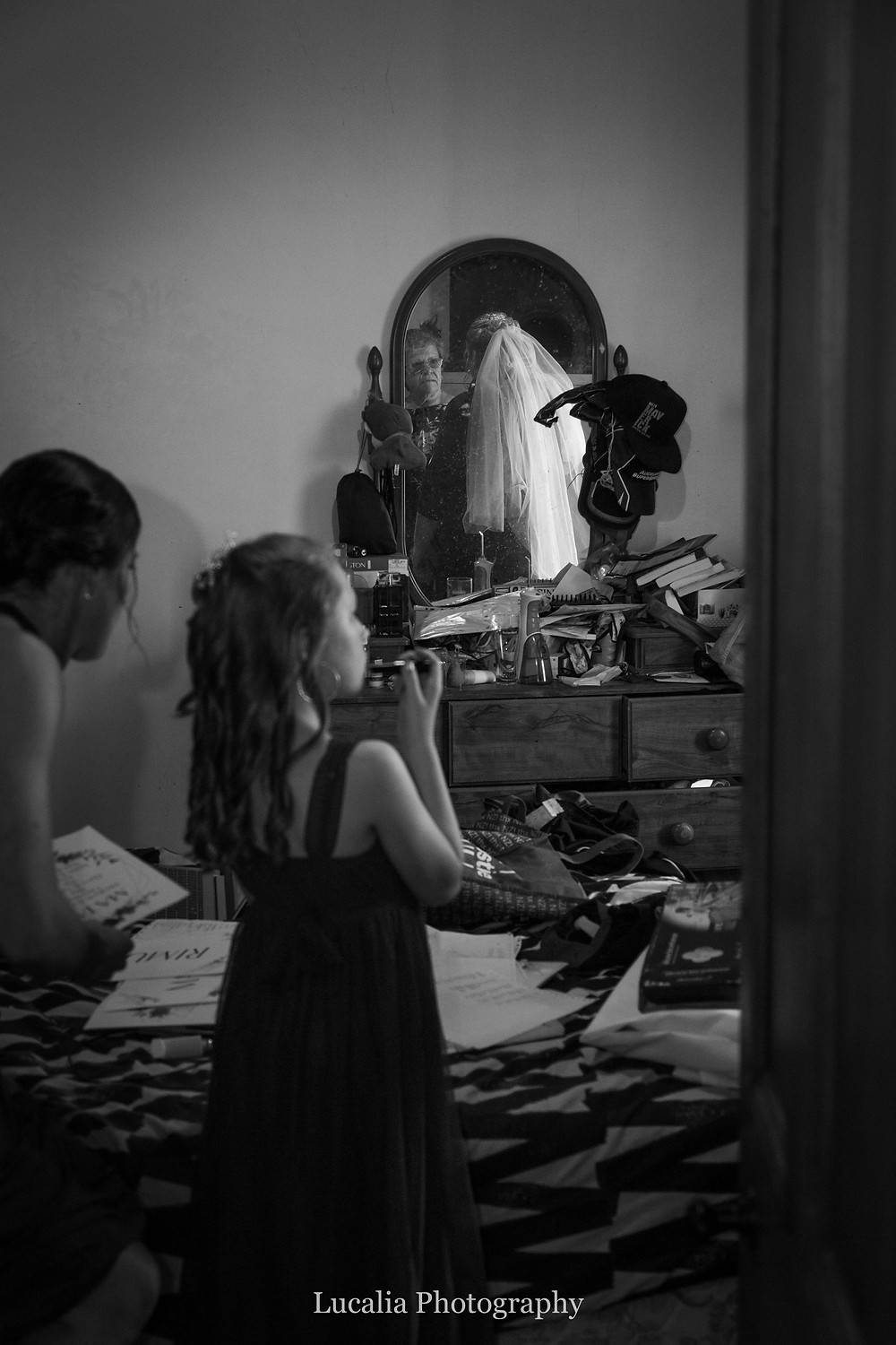 mother of the bride and bride reflected in bedroom mirror with flower girl and bridesmaid in the foreground, Wairarapa wedding photographer