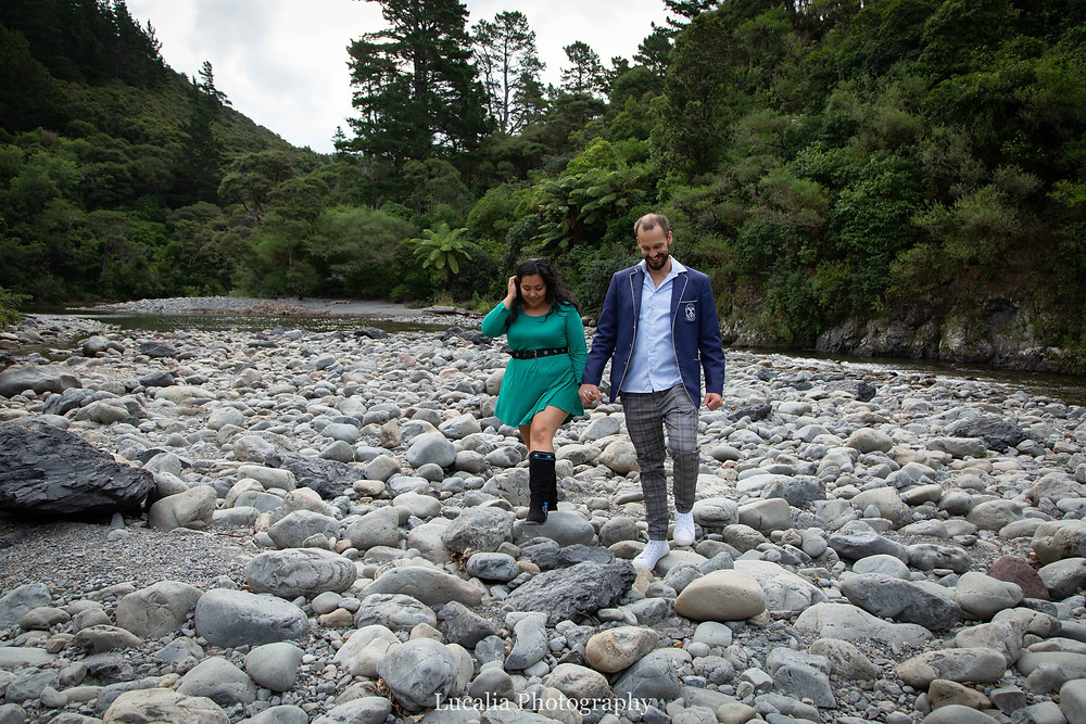 engaged couple walking over rocks next to Tauherenikau River, Wairarapa