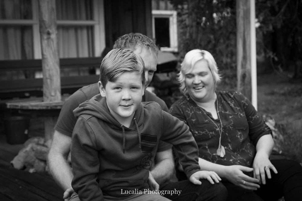 son sitting on father's lap with mum in background, Wairarapa family photographer