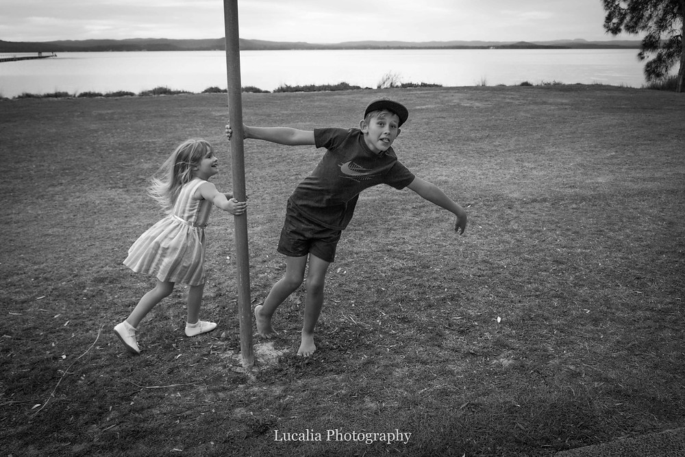 brother and sister playing around a pole with lake in the background, Wairarapa family photographer what to wear