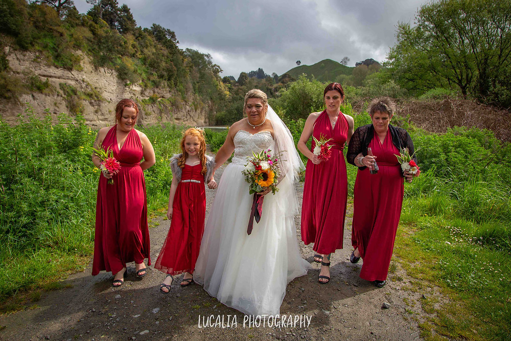 bride with her bridesmaids walking down gravel path with trees, Wairarapa wedding photographer