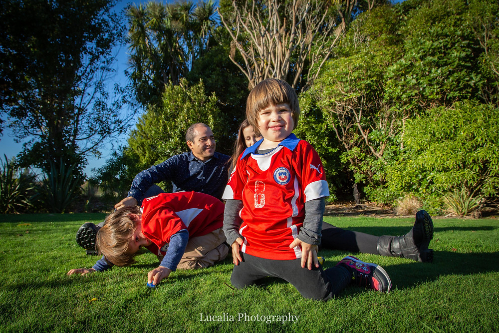 one child sitting up, another child crouching down with parents in background, sitting on the grass, Wairarapa family photographer