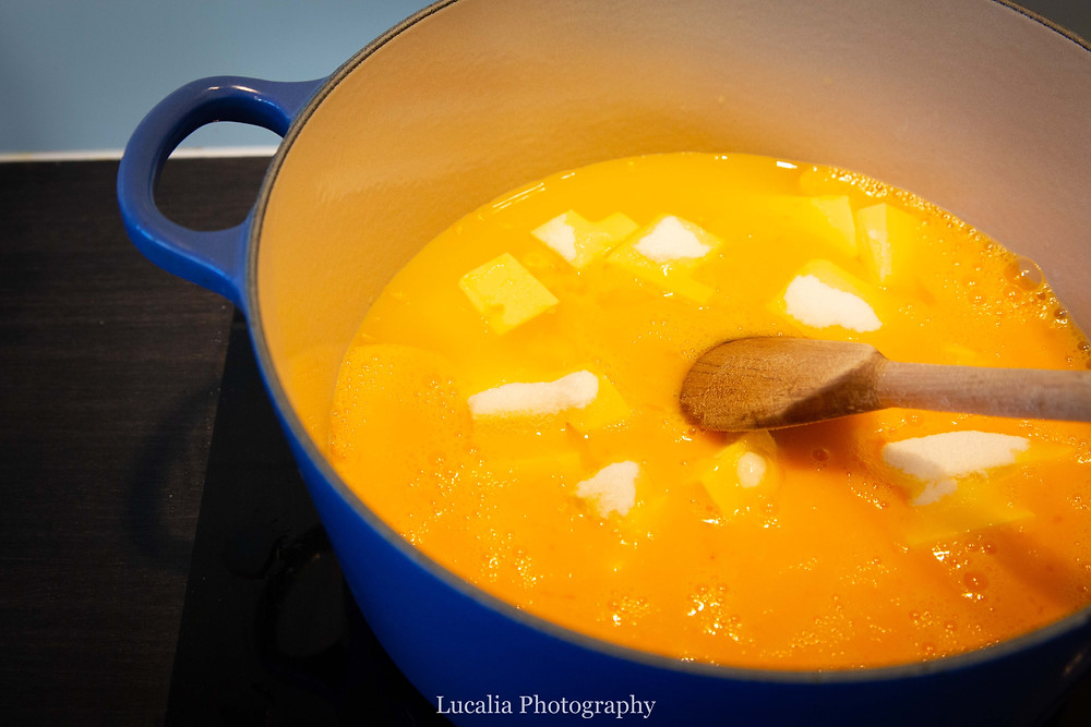 lemon curd cooking in a blue cast iron pot with a wooden spoon, Lucalia Photography
