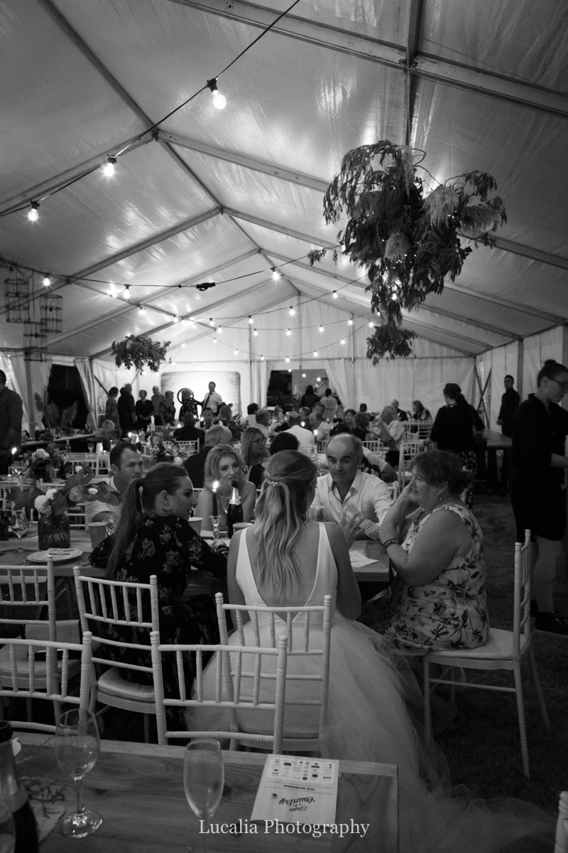 bride and guests sitting down at night marquee wedding, Wairarapa