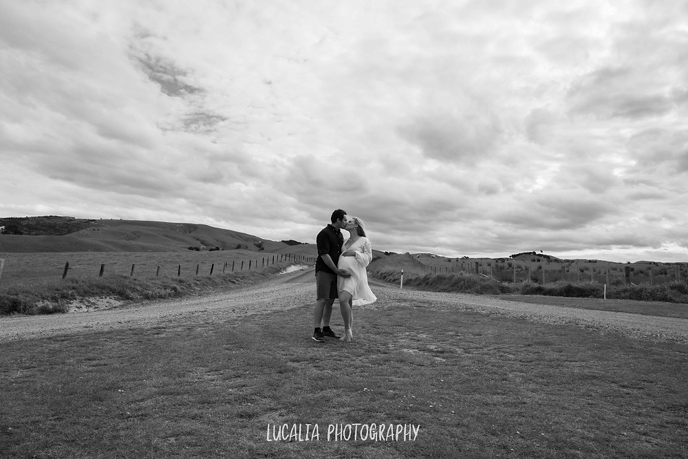 pregnant couple kissing with big sky, Wahi Falls, Tararua, Lucalia Photography