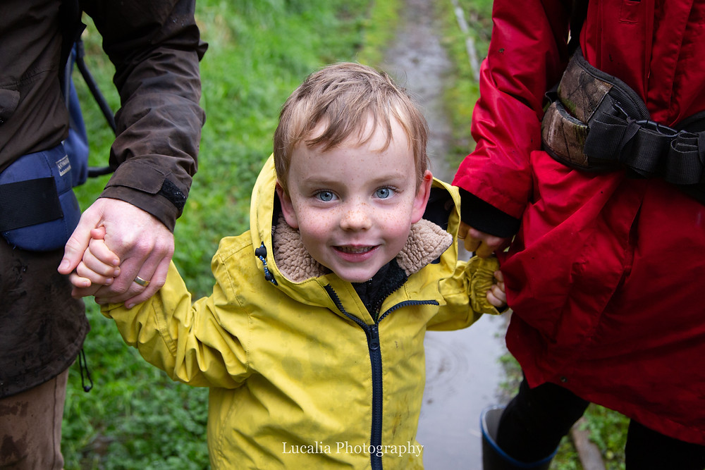 son holding hands with his parents on a rainy bushwalk, Wairarapa family photographer