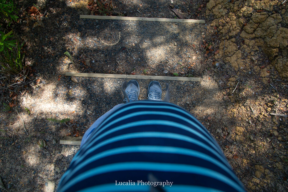 pregnant belly with walking shoes on gravel stairs