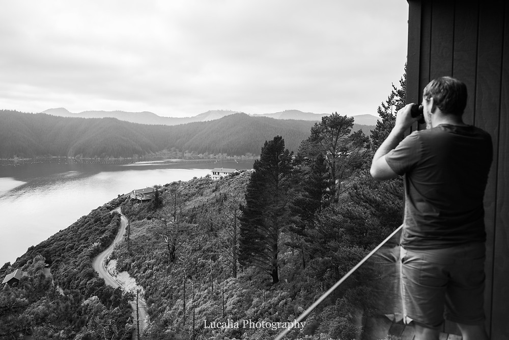 Husband looking through binoculous over forest to a bay, Wairarapa photographer