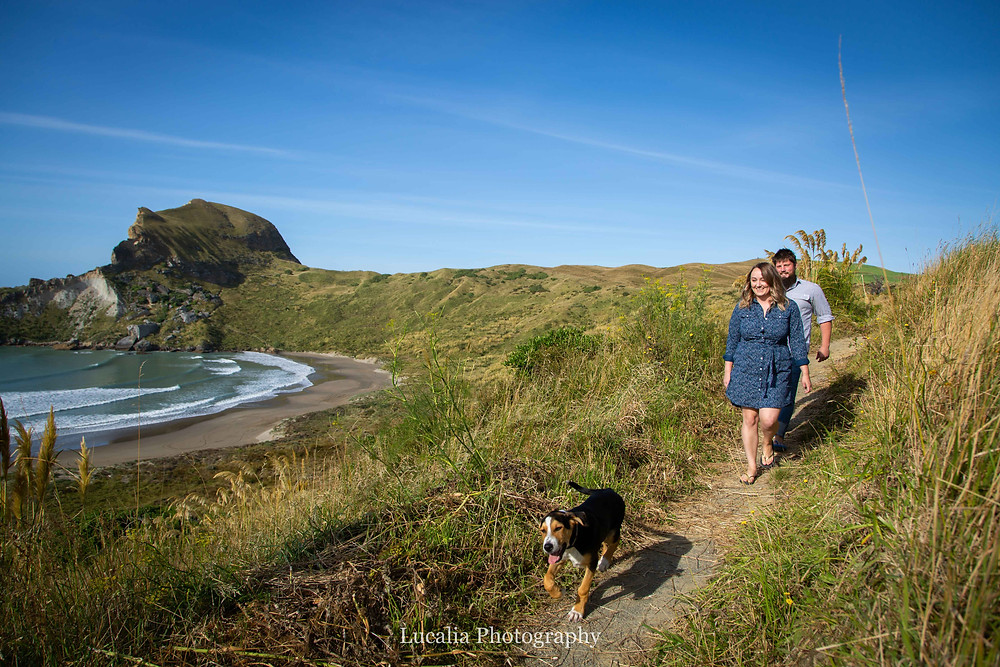 engaged couple and their dog walking at Castlepoint, Wairarapa