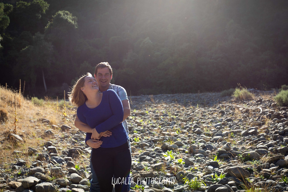couple hugging with forest and river stones, Martinborough Wairarapa wedding photographer