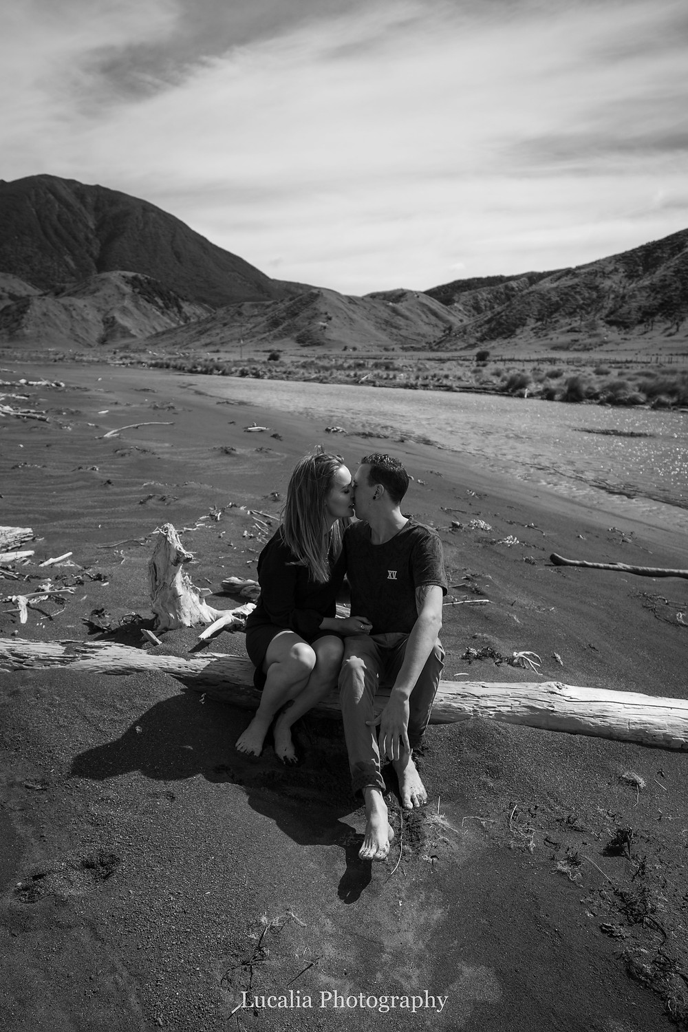 engaged couple kissing sitting on a driftwood log with mountains in the background, Wairarapa wedding photographer