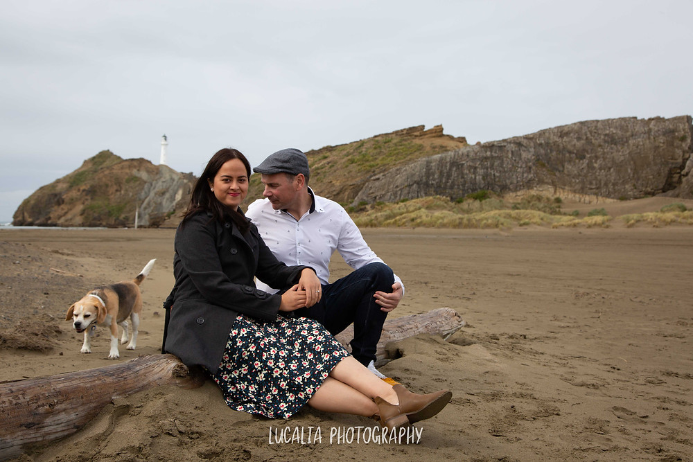 engaged couple sitting on the beach with their dog at Castlepoint lighthouse, Lucalia Photography Wairarapa wedding photographer