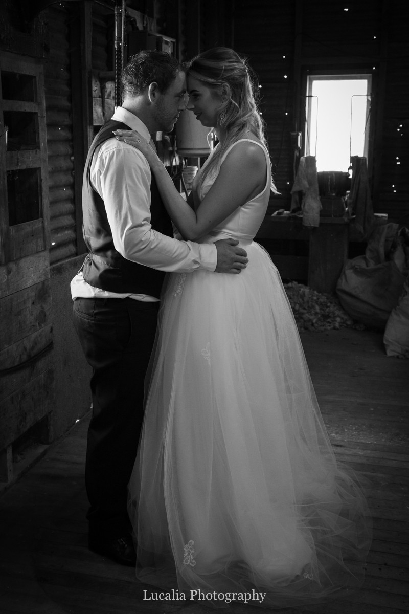 bride and groom hug inside a woolshed, Wairarapa