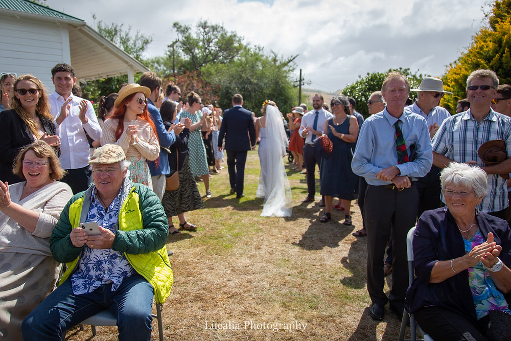 walking past clapping guests after wedding ceremony, Wairarapa wedding photographers