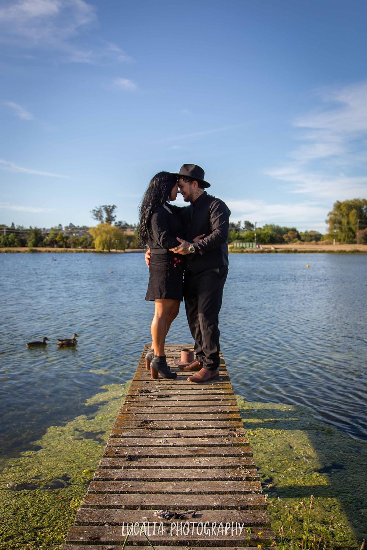 engaged couple hugging on jetty at Henley Lake, Wairarapa wedding photographer