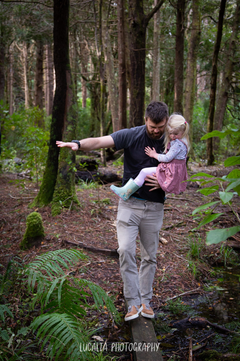dad holding daughter balancing on a log in Kiriwhakapapa forest, Wairarapa family photographer
