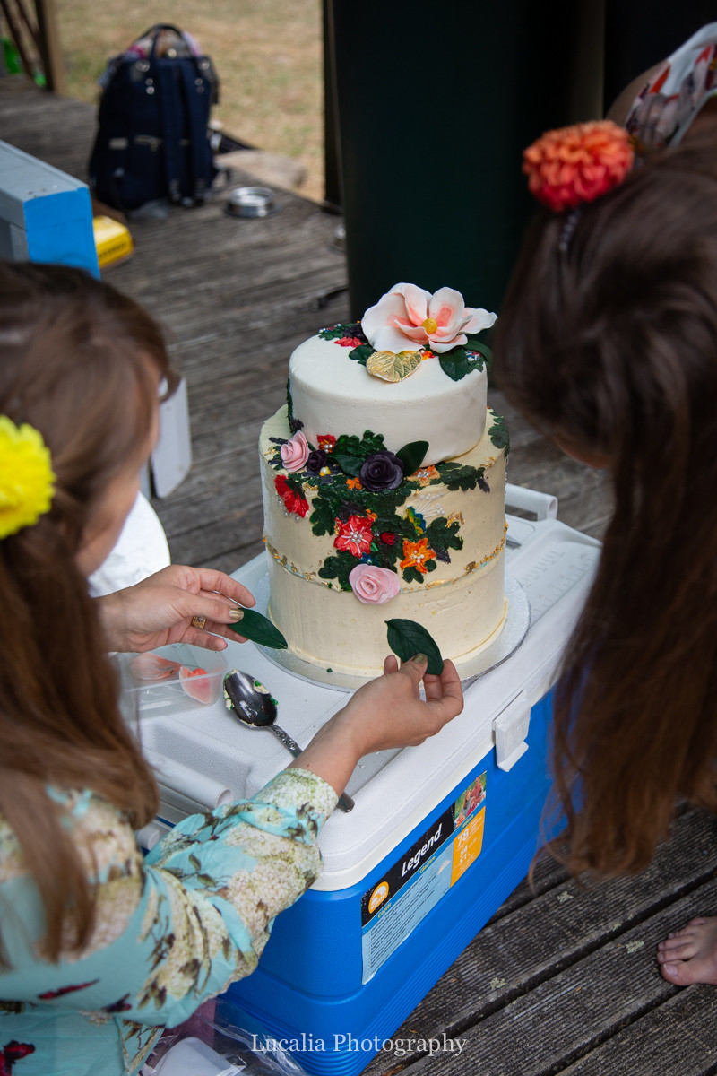 family putting finishing touches on wedding cake, Wairarapa wedding photographers