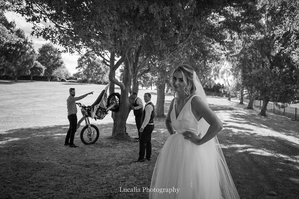 bride with groom, guys and motorbike in background, Wairarapa wedding photographer