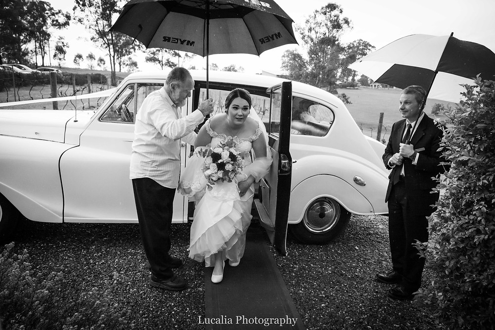 black and white photo of a bride getting out of a wedding car in the rain with umbrellas, Lucalia Photography