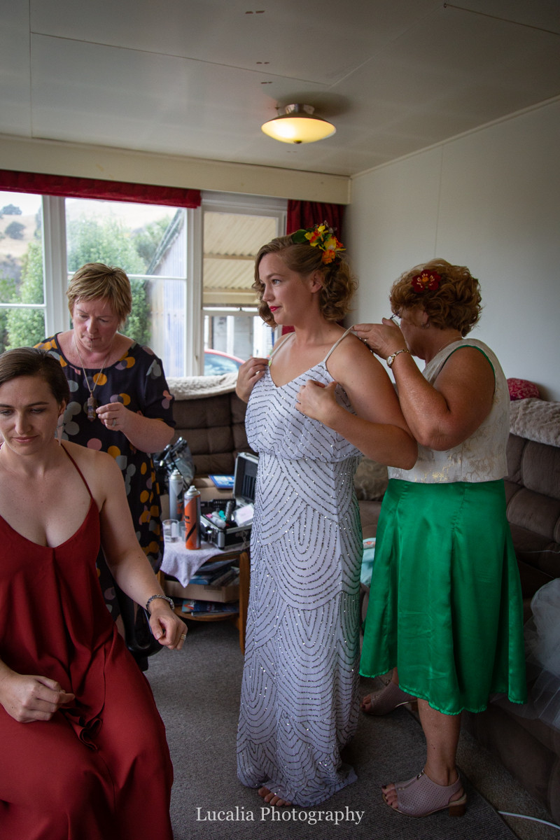 mother and bridesmaid help bride into wedding dress, Wairarapa wedding photographers