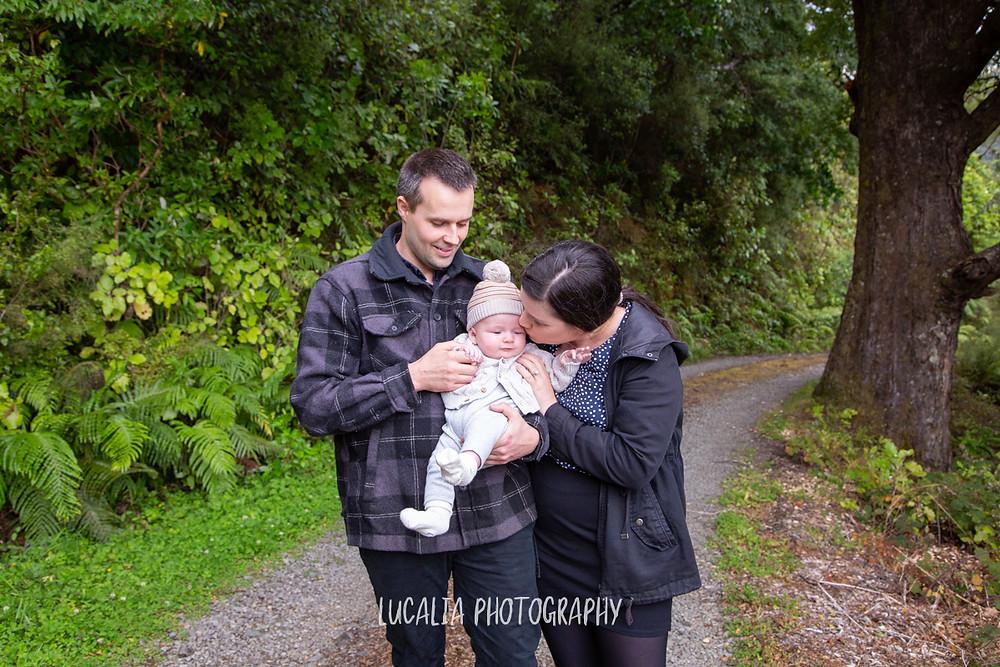 mum kissing baby held by dad on bush gravel road, Mount Holdsworth, Wairarapa family photographer
