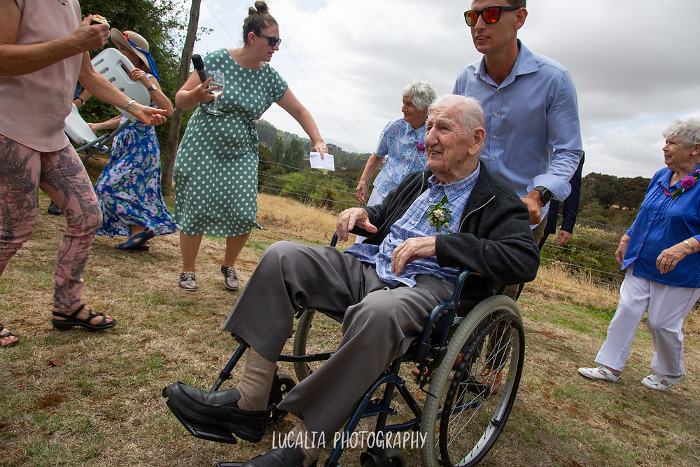 grandfather in a wheelchair being pushed across grass at a wedding, Wairarapa wedding photographer