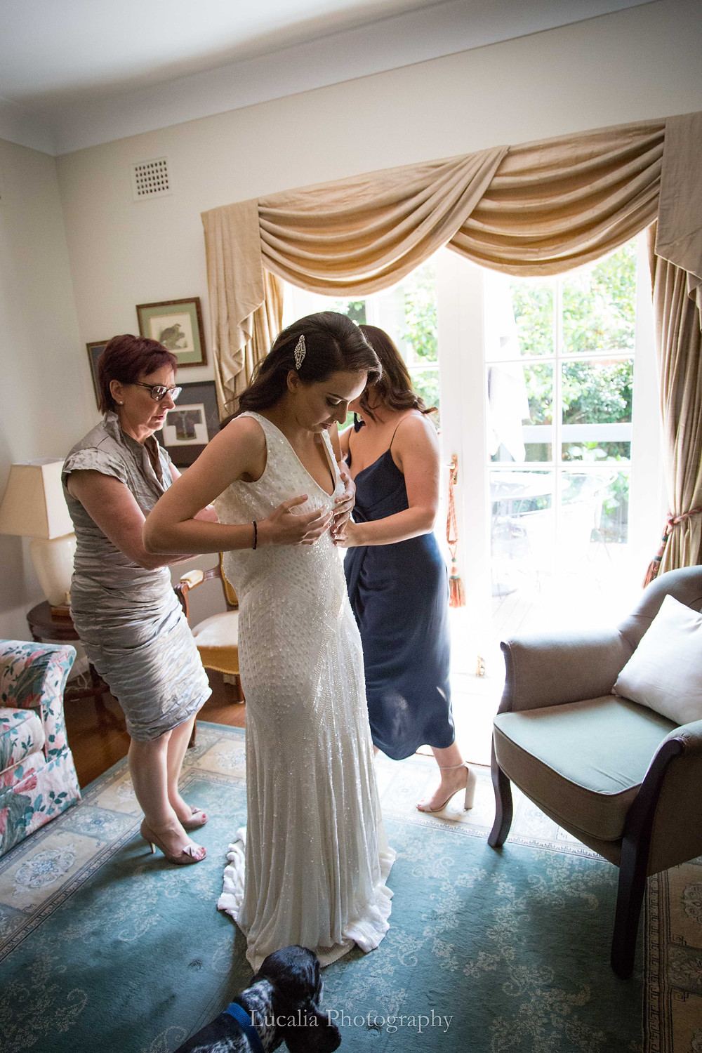 bride getting into her wedding dress helped by her mum and chief bridesmaid