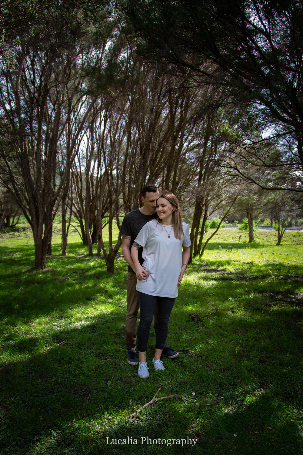 engaged couple standing in shady trees on a riverbank, Wairarapa wedding photographer