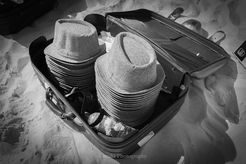 hats in a suitcase on a beach for wedding guests to wear