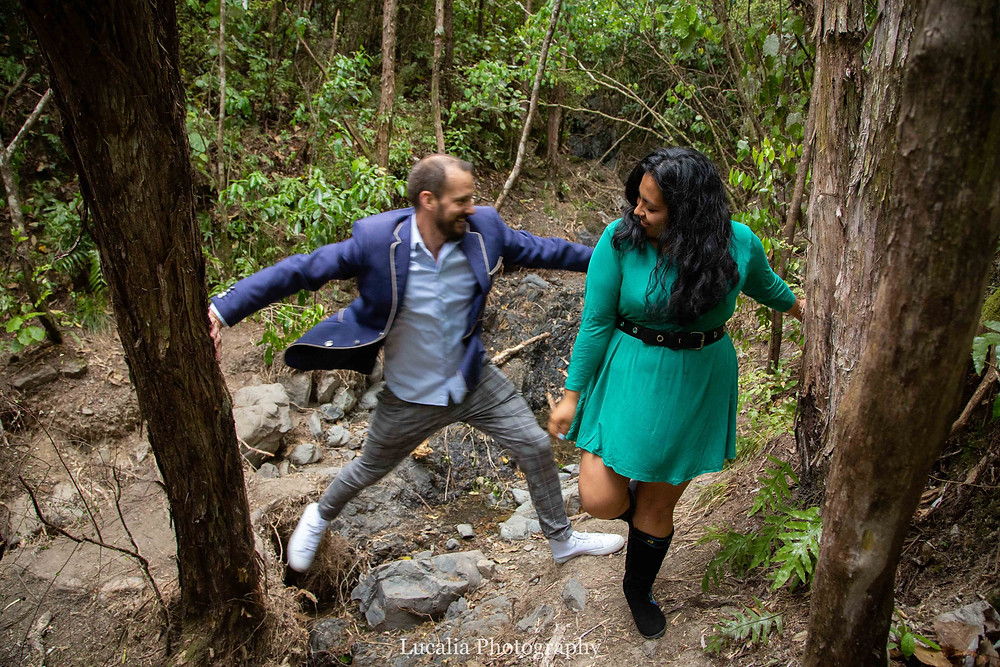 engaged couple jumping across a ditch in a forest, Wairarapa