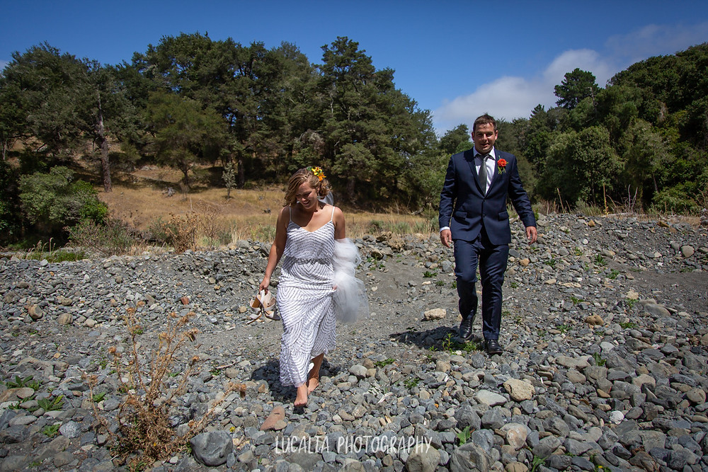 bride and groom walking over rocks with trees on their wedding day, Wairarapa wedding photographer