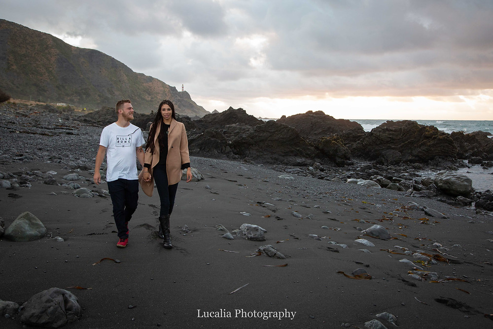engaged couple walking along a grey beach at sunrise with Cape Palliser lighthouse in the background, Wairarapa