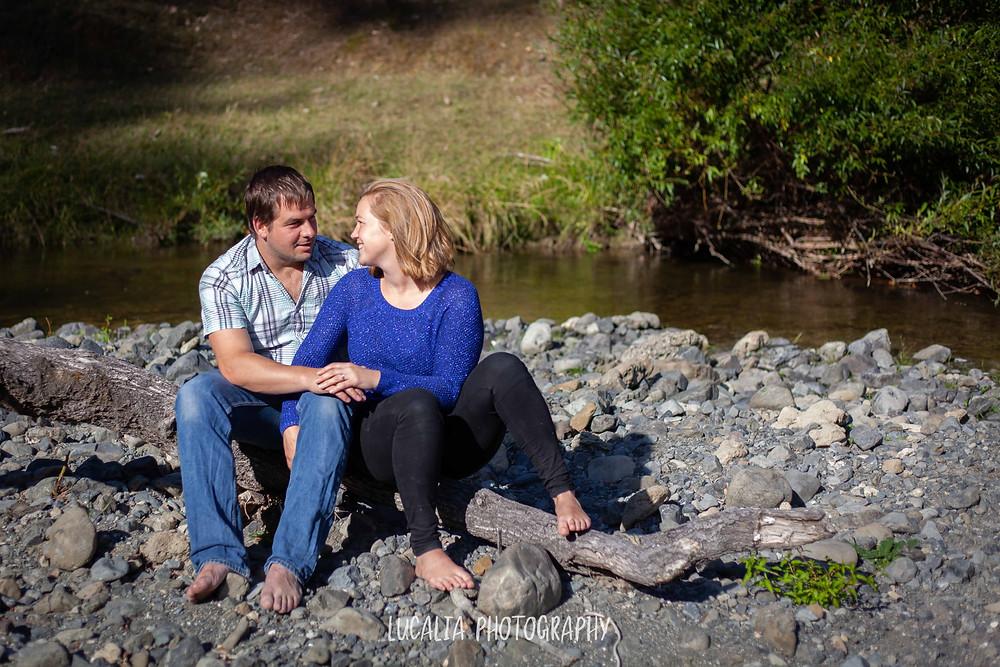engaged couple sitting on a log on a river bank, Martinborough Wairarapa wedding photographer