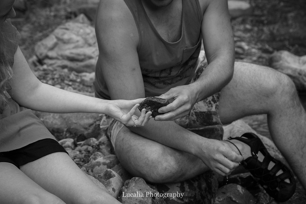 engaged couple sitting on a river bank discovering a pretty rock, Featherston Wairarapa