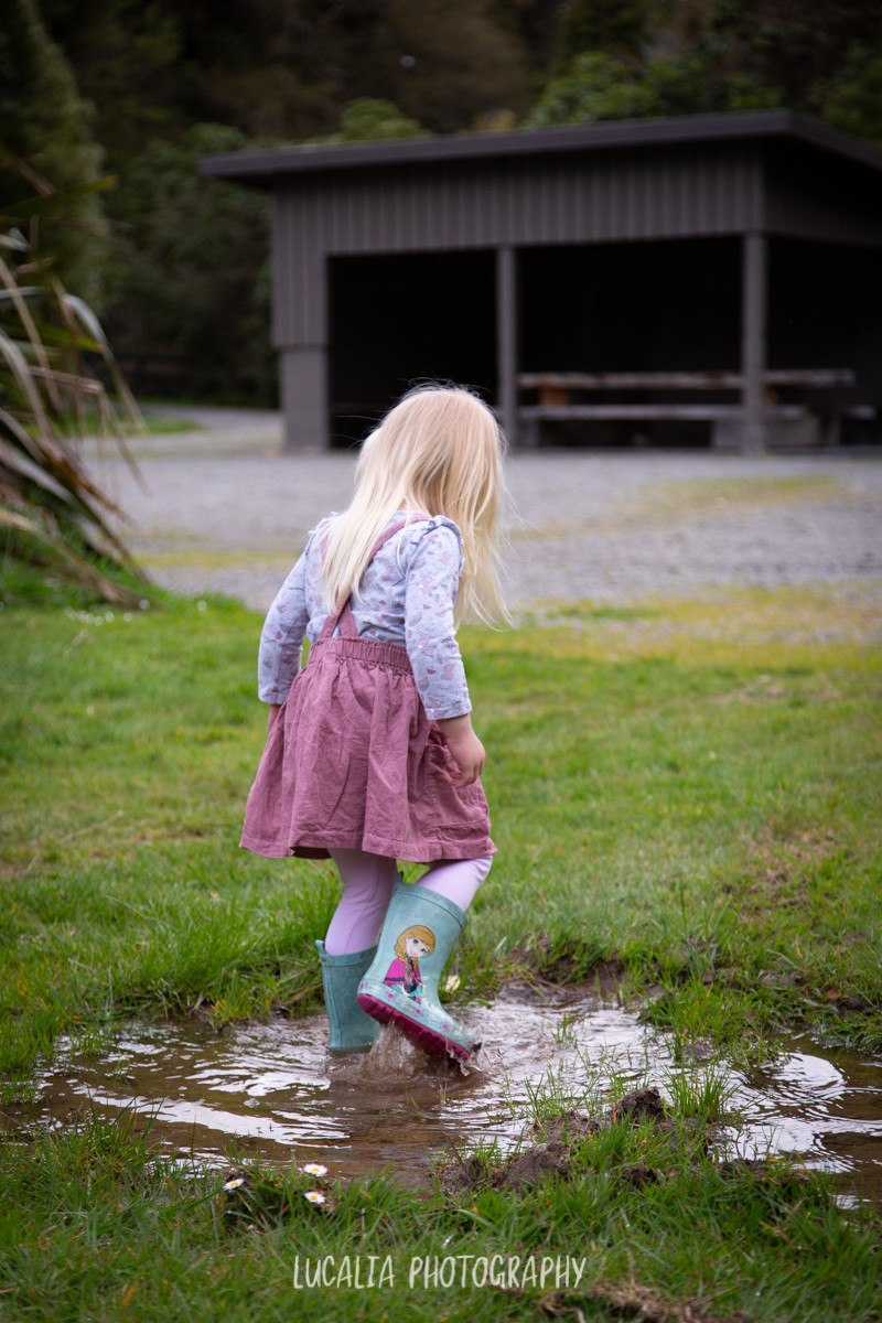 girl walking away splashing in puddle, Wairarapa family photographer
